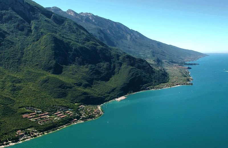 High angle view of lake garda and mountains against sky