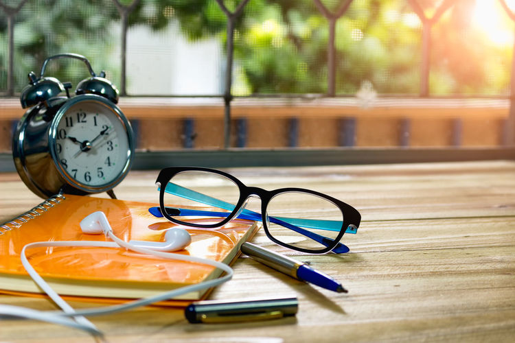 Close-up of eyeglasses with diary and alarm clock on table