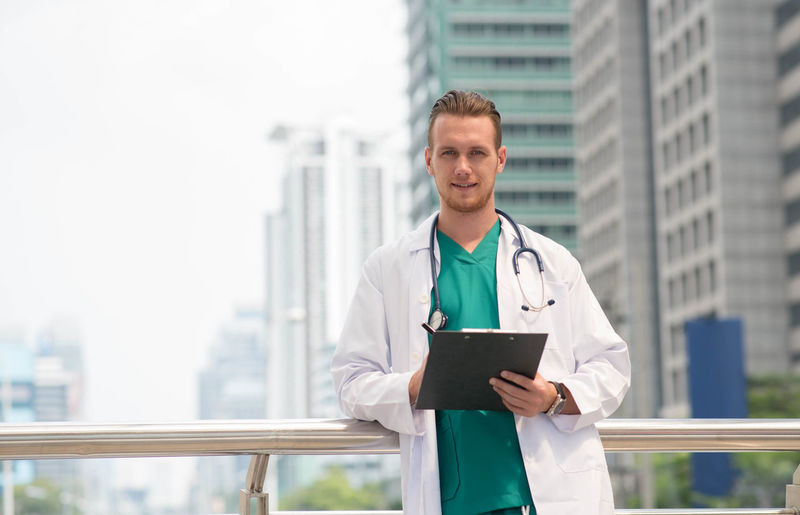 Architecture Occupation Waist Up City Standing One Person Doctor  Building Front View Built Structure Building Exterior Men Clothing Adult Holding Lab Coat Day Digital Tablet Healthcare And Medicine Office Building Exterior Skyscraper