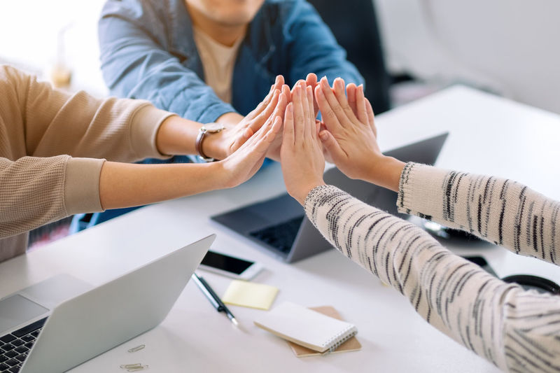 Midsection of colleagues joining hands over office desk
