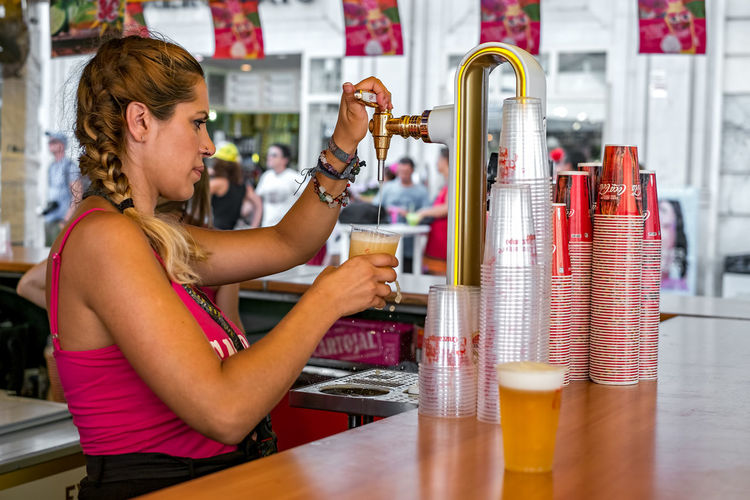 Malaga, Spain - August 12, 2018. A Spanish woman fills a glass of beer at the Feria de Malaga, an annual event that takes place in mid-August and is one of the largest fiestas in Spain 2018 Andalucía Malaga SPAIN Spanish Spanish Style Spanish Woman Adult Alcohol Bar - Drink Establishment Bar Counter Bartender Beer Beer - Alcohol Beer Glass Business Coca Cola Drink Drinking Glass España Feria De Malaga Fiesta Food And Drink Glass Hairstyle Happy Hour Holding Household Equipment Indoors  One Person Plastic Glass Refreshment Side View Spanish Culture Spanish Fiesta Spaın Waist Up Women EyeEmNewHere Summer In The City
