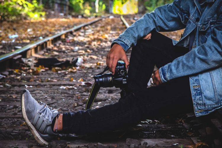 Aesthetic shot Ultra Boost Train Train Tracks Real People One Person Focus On Foreground Lifestyles Outdoors Men Day Technology Close-up Human Hand Forest Tree Trees Camera Nikon Jean Jacket Shoe