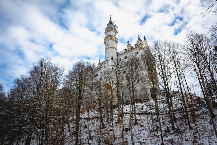 SCHWANGAU, BAVARIA, GERMANY - NOVEMBER 17, 2017: Neuschwanstein castle view in winter against blue sky Low Angle View Built Structure Sky Tree Architecture Nature Place Of Worship Cold Temperature Cloud - Sky Building Exterior Snow Plant Winter Spirituality No People Bare Tree Building Outdoors Spire  Neuschwanstein Neuschwanstein Castle Castle Castles Germany Dramatic Sky