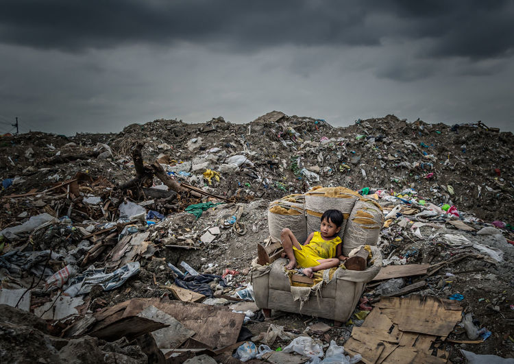 Man with umbrella and garbage against sky