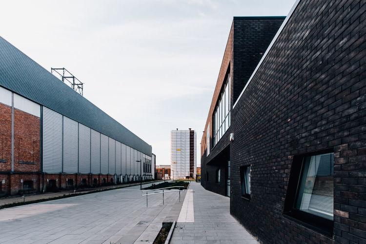Empty street amidst buildings against sky