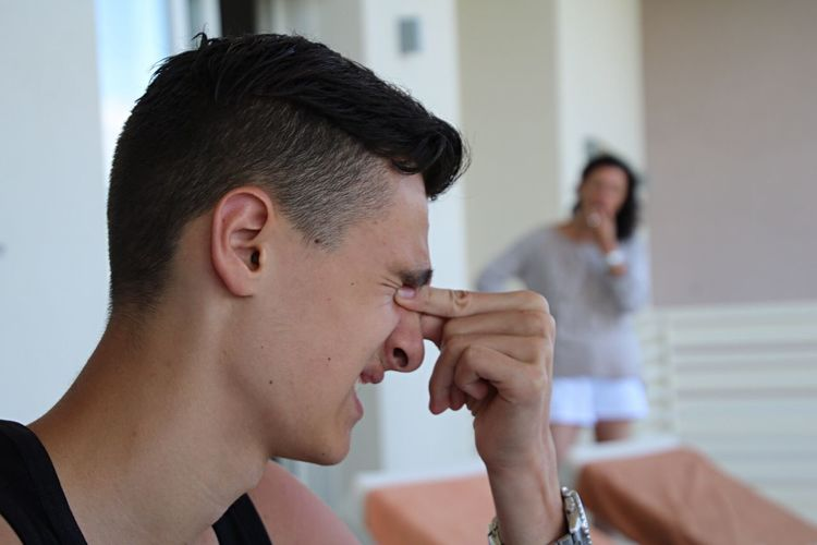 Young man rubbing eyes while mother standing by wall at home