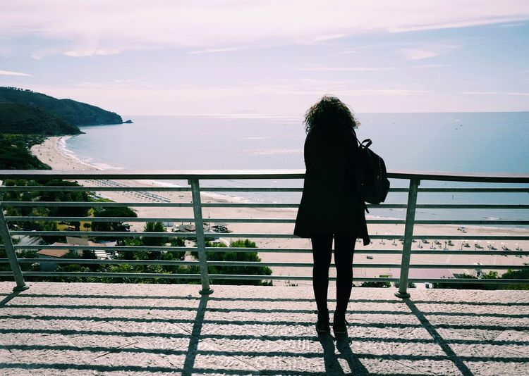 Rear view of silhouette woman standing by railing against sea