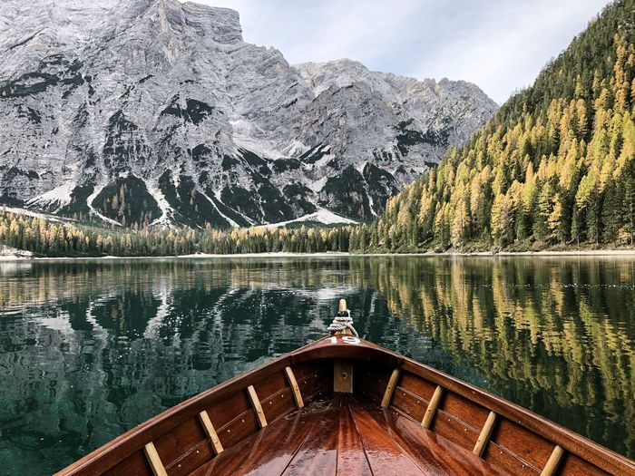 Boat on lake against snowcapped mountain