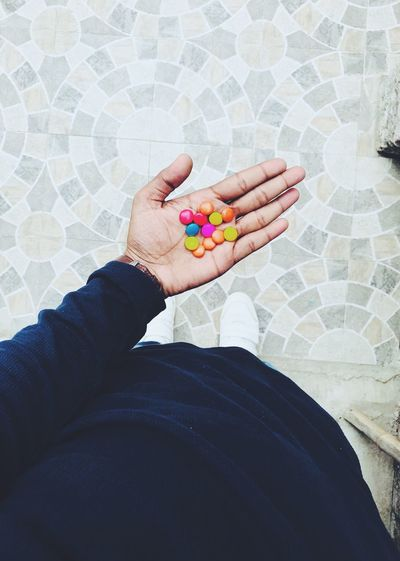 Cropped hand of person holding multi colored candies
