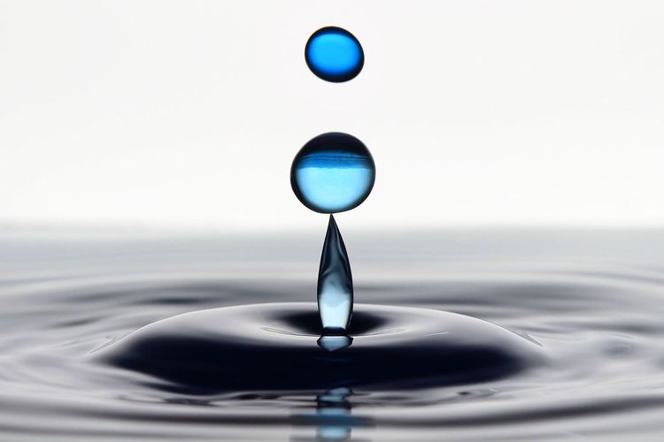 Close-up of droplets falling on water against white background