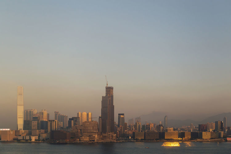 Modern buildings by sea against clear sky