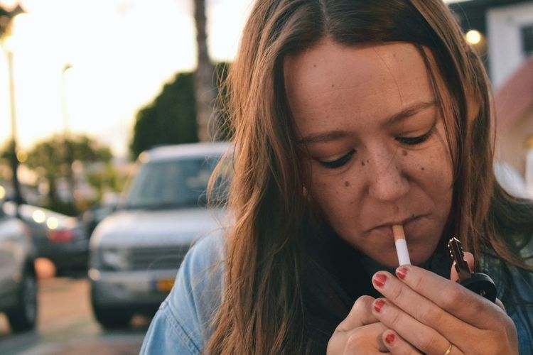Close-up of mid adult woman smoking cigarette during sunset