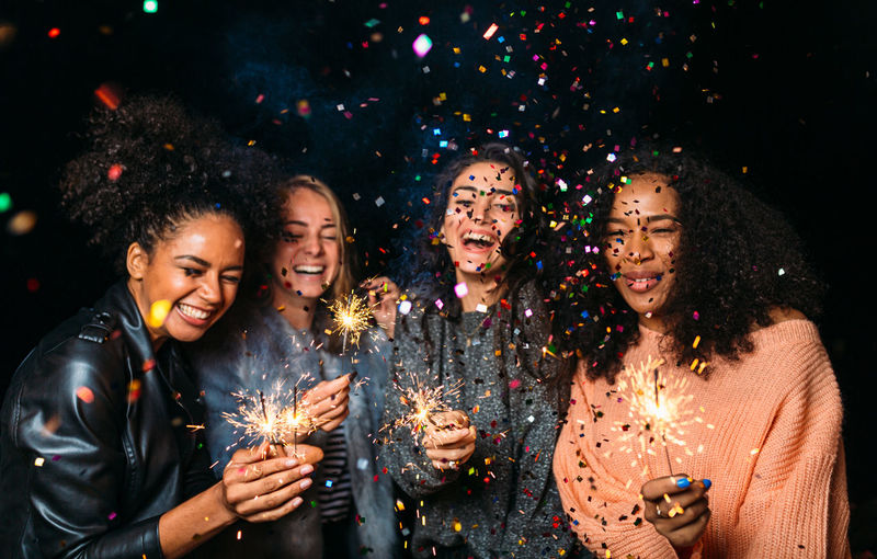 Friends holding sparklers at party