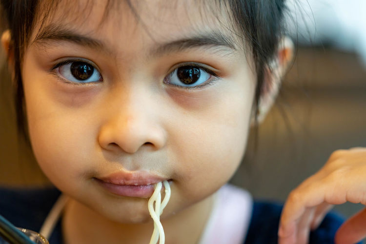 Close-up portrait of cute girl eating food