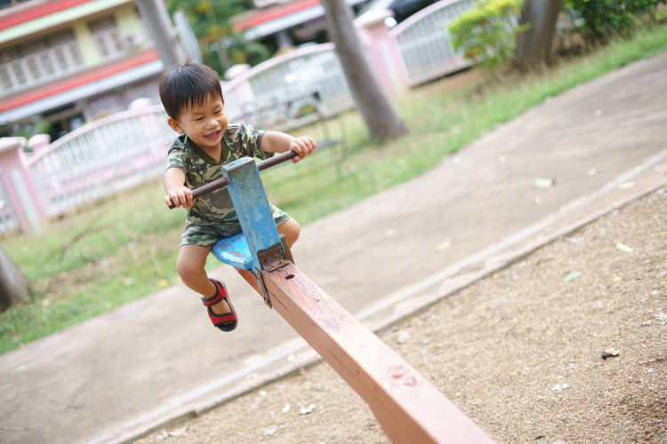 Cute boy playing on seesaw at playground