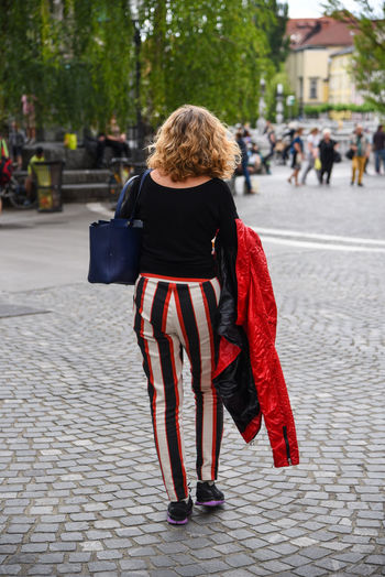 Striking stripes! Fashion Lady Red Striking Fashion Stylish Woman Adult Blond Hair Cultural Heritage Curly Hair Day Full Length Incidental People Leisure Activity Lifestyles One Person Outdoors People Real People Rear View Striped Pattern Walking Warm Clothing Young Adult Young Women