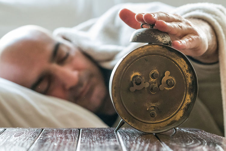 Man touching alarm clock while sleeping on bed at home