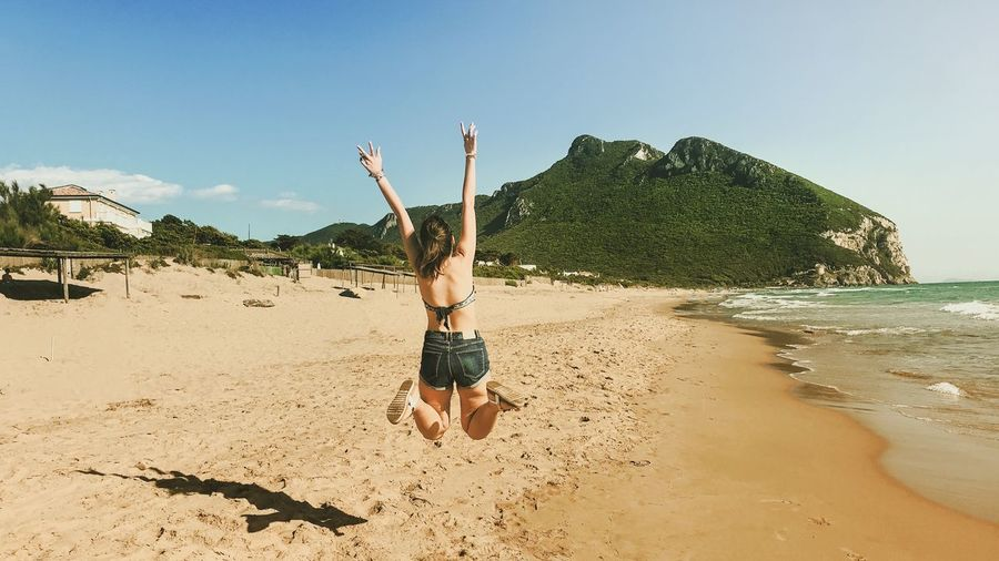 Rear view of woman with arms raised jumping at beach against sky
