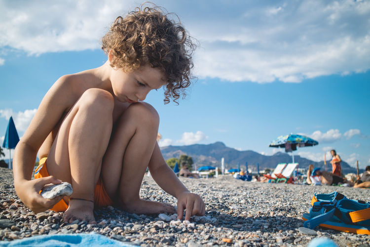 Shirtless Boy Playing With Pebbles On Beach Against Sky