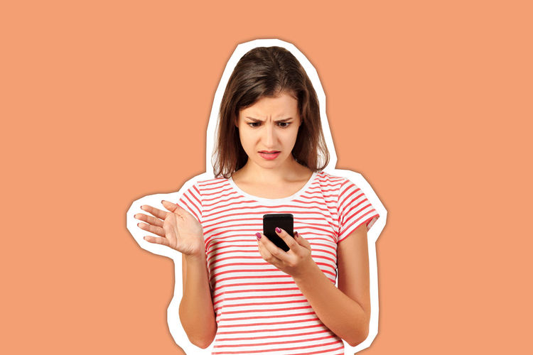 Young woman using mobile phone against orange background