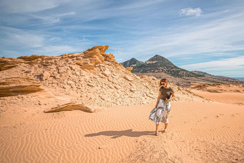 Full length of woman on arid landscape against sky