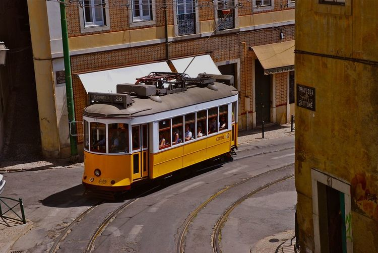 Yellow tram on road against buildings