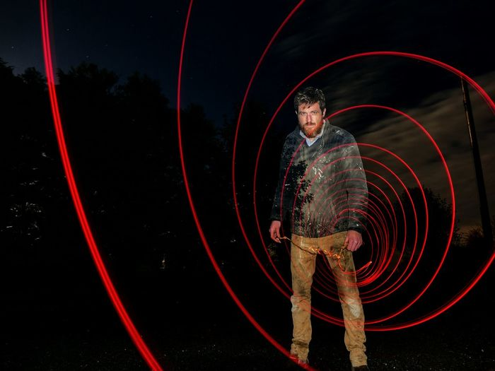 Portrait Of Man Standing By Light Painting At Night