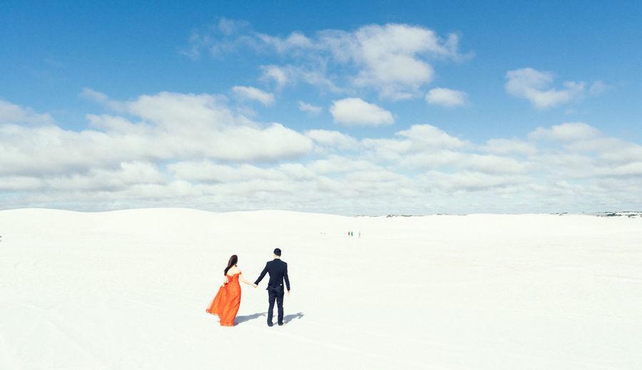 Couple walking on snowy landscape against sky