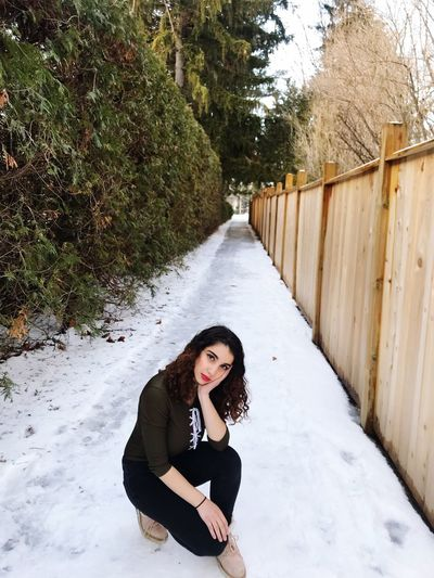 Portrait of young woman crouching on snow covered road