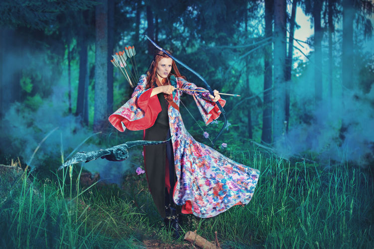 Young Woman Hunting With Archery Bow In Forest