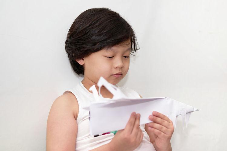 Portrait of a boy play plane paper