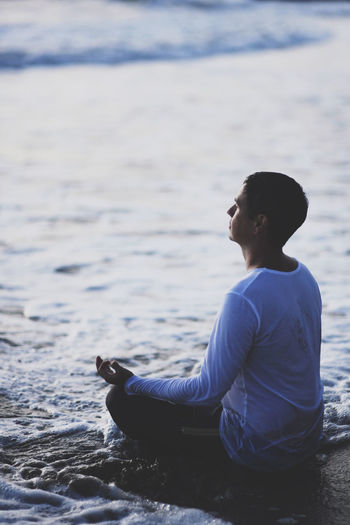 Man meditating while sitting at beach during sunset