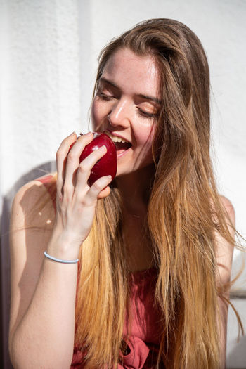 Young joyful attractive woman in casual summer dress sitting on balcony and eating tasty juicy red apple Woman Girl Apple Eating Happy Smiling Balcony Terrace Summer Young Female Joy Cheerful Beautiful Attractive Portrait Pretty Charming Sensual 💕 Cool Casual Dress Food Fruit Healthy Tropical Ripe Tasty Sweet Juicy Fresh Organic Natural Vitamins Sitting Holding Plants Pots Indoors  Copy Space