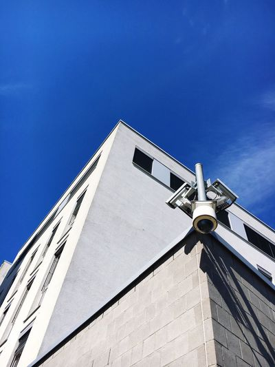 Low angle view of security camera on building against blue sky