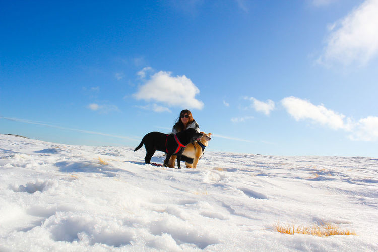 People with dog on snow against sky