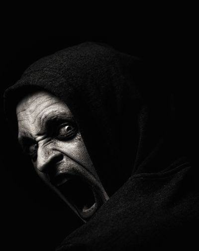 Portrait of scary man shouting against black background