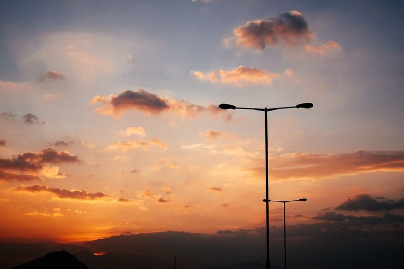 Low angle view of street light against cloudy sky