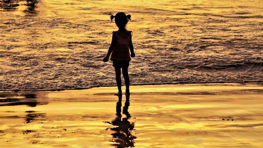 Full length of woman standing on beach during sunset