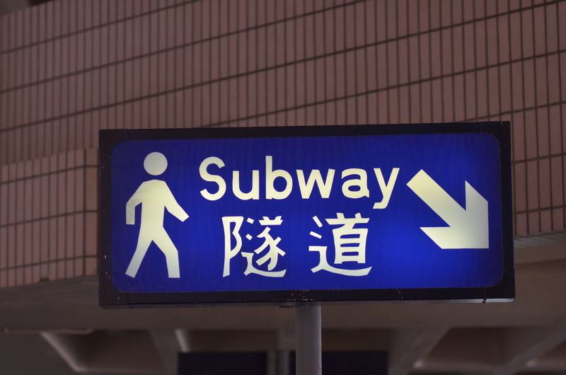 A Subway sign in Hong Kong Sign Signage Architecture Arrow Symbol Blue Close-up Direction Directional Sign Honk Kong Information Information Sign Sign Subway Symbol Text