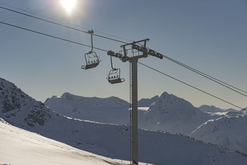 Mountain Winter Sky Cold Temperature Snow Mountain Range Cable Car Sunlight Snowcapped Mountain Low Angle View No People Lens Flare Chairlift Morning Empty Chair Anticipation Expectation Morning Light Tranquil Scene Mountain Peak Whistler Blackcomb Opening Soon Day Outdoors