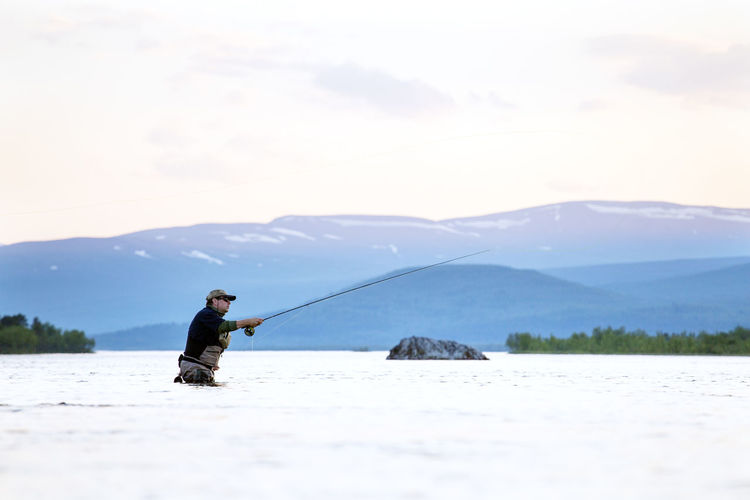 Man fishing in lake against mountain range