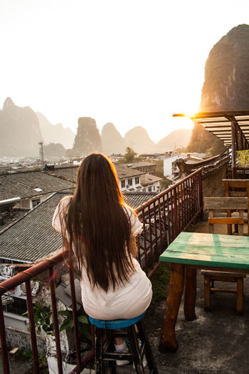 Yangshuo, china mountainous landscape exotic asian sunset watching sunset on the roof of the house.
