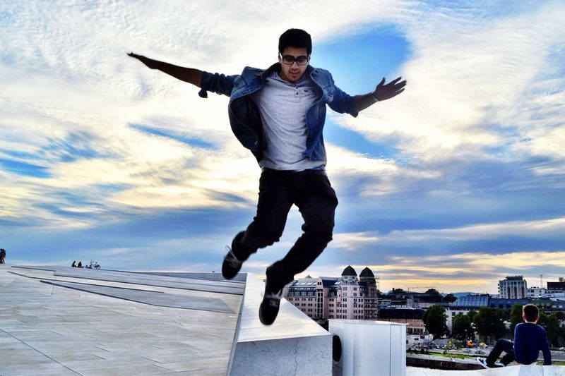 Young man jumping against sky in park