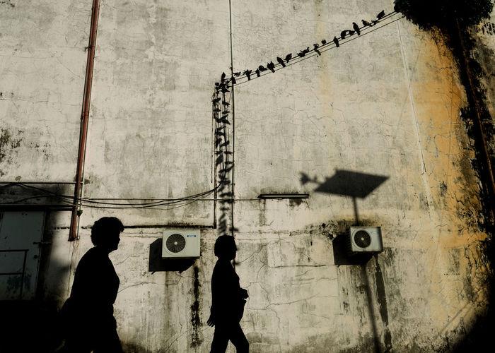 Silhouette people walking by building