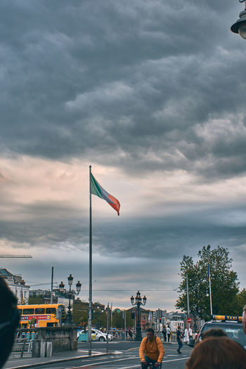 Flags on street against sky in city