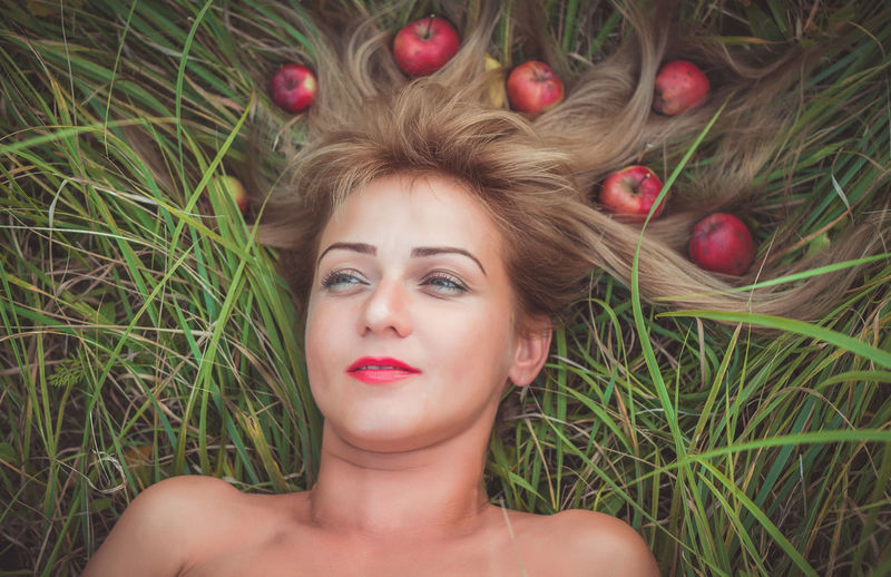 Woman laying on green grass with loose hair with apples Hairstyle Outdoors Leisure Activity Lying On Back Real People Looking At Camera Lifestyles Nature Women Front View Grass Beauty Young Women Headshot Lying Down Beautiful Woman Young Adult Plant One Person Portrait Freshness