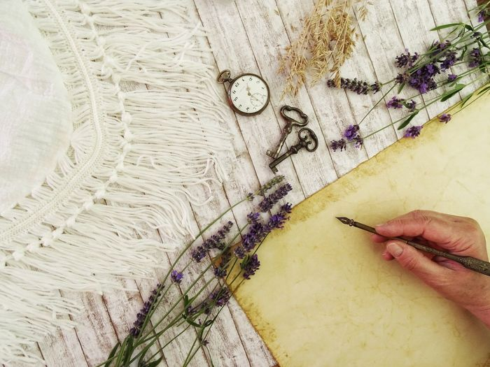Close-up of person writing on paper with antique pen