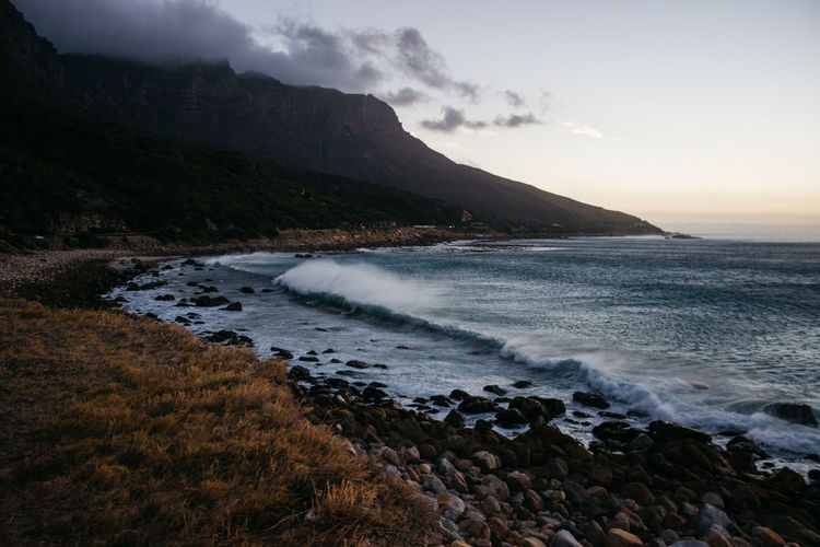 Blue hour magic. Wallpaper Backgrounds Landscape Beauty Beauty In Nature Wave Waves Ocean Sea Clouds Clouds And Sky Jonnynichayes Cape Town Adventure Explore Calm Outdoors Nature Scenics Seascape Mountains Tranquility Tranquil Scene Dark Typography