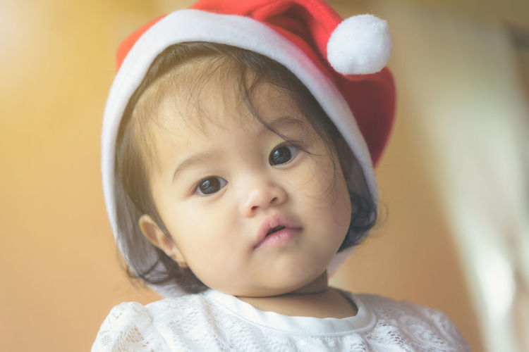 Little Asian girl wearing a Santa Cross hat. Has a cute and innocent look. Baby Babyhood Child Childhood Close-up Clothing Cute Front View Headshot Human Face Indoors  Innocence Looking Looking Away One Person Portrait Real People Toddler  Young