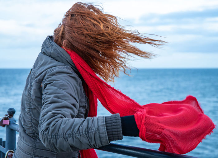 A woman stands by the sea in strong winds. concept stormy weather